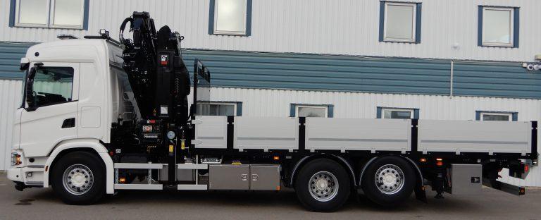 Scania G450 6x2 4,75. Fast flak Åkarnas med plyfagolv och surrskenor i fullbredd. Utdragbara stegar fram, utdragbara lämstöd bak för bakläm. Kran Hiab 358 E-6 med Jib. Variabelt system med hydraulpump SVH 112, hydraultank rostfri, verktygslådor och stakrörslåda.